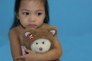 Gift im Spielzeug; Kind mit Teddybär