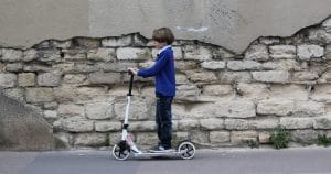 Kind auf Scooter Tretroller